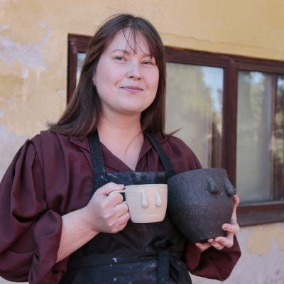 Riikka Väänänen käsissään tissikahvikuppi ja tissikukkaruukku.