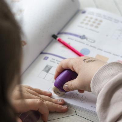 Lapsi pyyhkii merkintöjä koulukirjasta.
