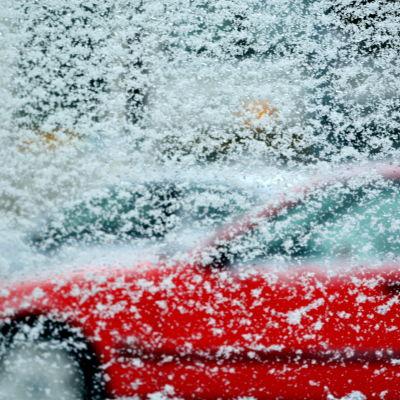 röd bil fotad genom fönstret på en bil