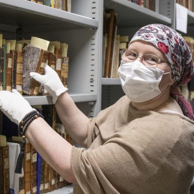 Virva Suvitie ottaa Valamon kirjaston hyllystä 1700-luvulta olevaa kirjaa.