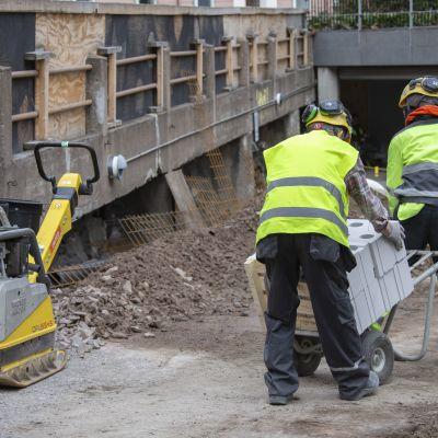 Två byggarbetare transporterar betongelement med en kärra på ett bygge