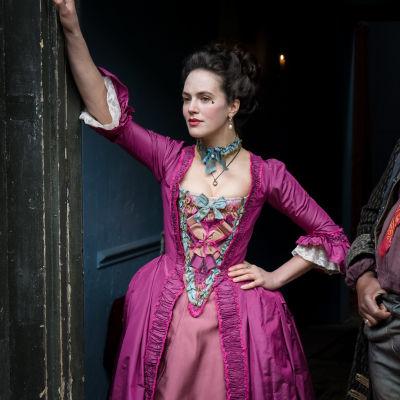 Harlotsin Charlotte porttikongissa pinkki mekko päällään.