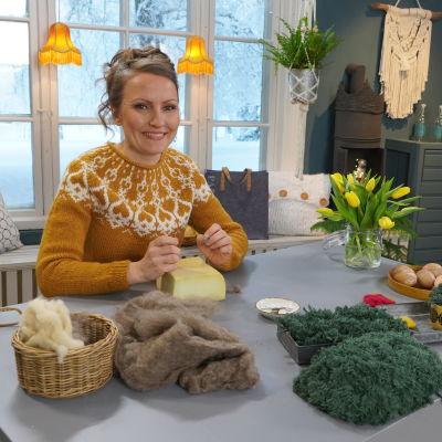 Lee sitter vid bordet i hobbyrummet. På bordet finns ull, skumgummi, nåltovingsnlar, tulpaner, ljus, ägg och påskgräs.