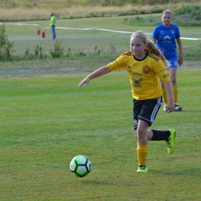 Sonja Karlsson, en fotbollsflicka i gul skjorta sparkar bollen i en matchen. I bakgrunden står lagkamraten Amelie Bärling.