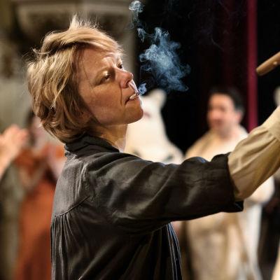 Närbild på Tove (Alma Pöysti) som har en cigarett i munnen samtidigt som hon målar en tavla.