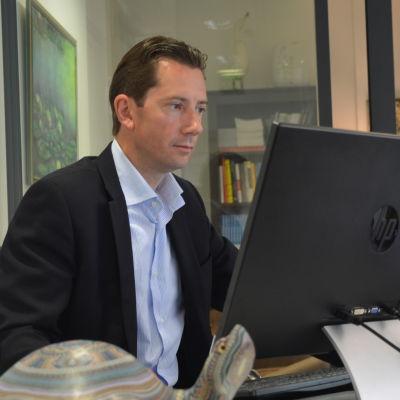 Jan D. Oker-Blom tittar på en skärm vid sitt arbetsbord.