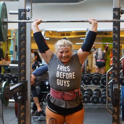 """Sara Dahlström står i ett gym och lyfter en stång med vikter ovanför sitt huvud. På hennes tröja står det """"Fries before guys""""."""