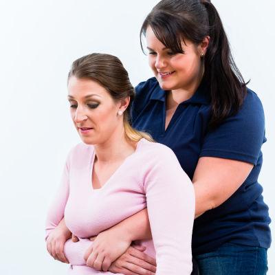 En kvinna gör Heimlichmanövern på en annan kvinna.