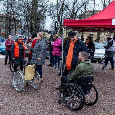 Rullstolar, hinder och deltagare framför ett stånd på Borgå torg.