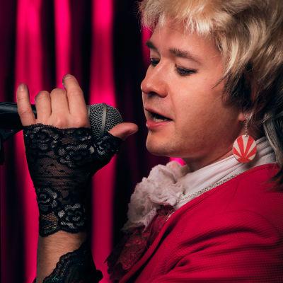 Neumanniksi pukeutunut näyttelijä laulaa mikrofoniin.