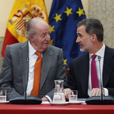 Juan Carlos och Felipe VI sitter bredvid varandra och ser på varandra.