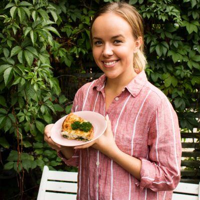 Näyttelijä Sara Parikka seisoo villiviiniseinän edessä ja pitää lautasta kädessään, lautasella on pala piirakkaa.