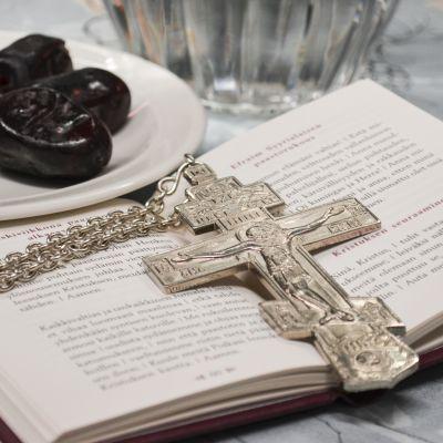 Vasemmalla taateleita lautasella, joiden vieressä näkyy vesikannun alaosa. Etualalla auki oleva kristillinen rukouskirja, jonka päälle on aseteltu metallinen ortodoksikristyn papin risti.