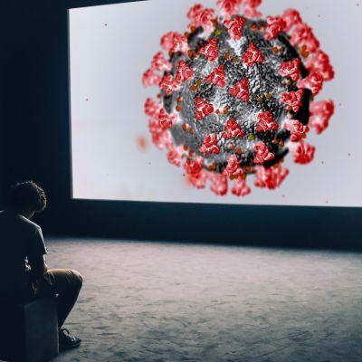 Mies istuu ja tuijottaa skriiniä, jolla näkyy koronavirus.