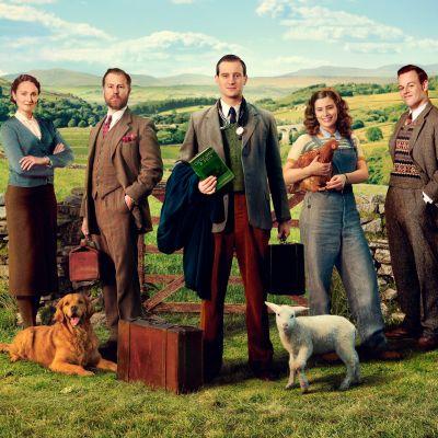 Viisi Kaikenkarvaiset ystäväni hahmoa seisoo nummella matalan kiviaidan edessä. Kuvassa myös lehmä, koira, karitsa, kukko ja kana.