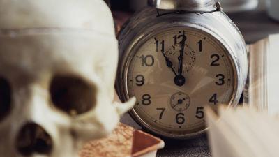 Dark academia -aiheinen asetelma kellosta, kirjoista ja pääkallosta.