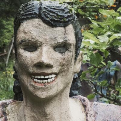 Naista esittävä patsas jolla tekohampaat ja lasisilmät.
