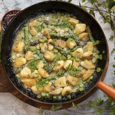 En stekpanna med gnocchi och sparris