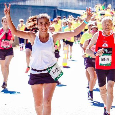 Maratonia juoksevat nainen ja mies näyttävät hymyillen voitonmerkkiä ja peukaloa kuvaajalle.