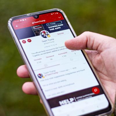 Käsi pitelee puhelinta, jossa on auki sosiaalisen median Parler-applikaatio.