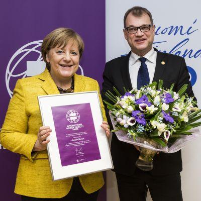 Juha Sipilä gav priset till Angela Merkel i Bryssel.