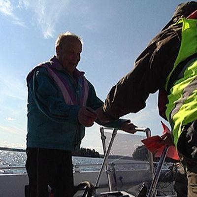 Valvoja tarkistaa kalastuslupaa asiakkaalta