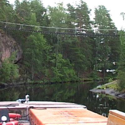 Repoveden vesibussi alittaa riippusiltaa luonnonpuistossa.