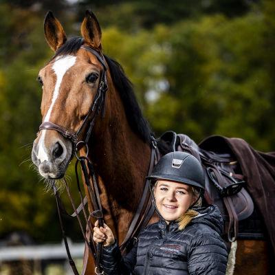 En ryttare bredvid en stor brun häst.