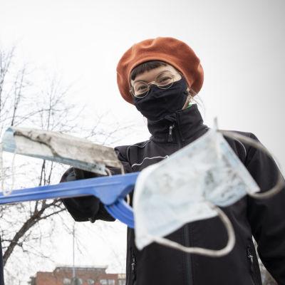 Eveliina Korkiatupa ja Juni Sinkkonen näyttävät roskapihdeillä maasta poimimiaan käytettyjä kasvomaskeja.