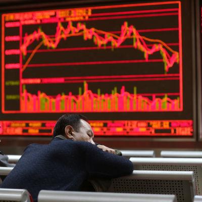 Ett par investerare sover i bänkarna i ett börshus, framför en skärm med nedåtgående kurvor.