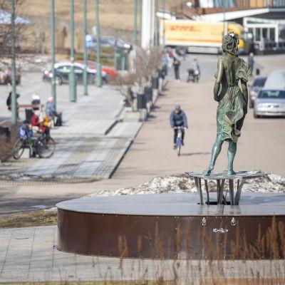 Ihmisiä ulkoilemassa Lappeenrannan satamassa ja katselemassa patsasta.