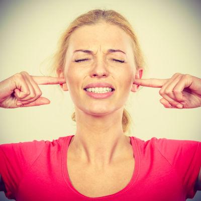En kvinna som satt fingrarna i öronen.