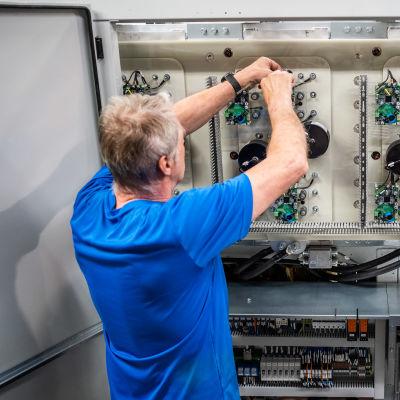 Sähköasentaja Jouni Valli asentaa terästeollisuuden energiatehokkuuskompensaattoria Merus Powerin tehtaalla Nokialla.