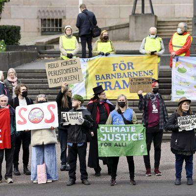 Människor demonstrerar utanför Ständerhuset 8.9.2021. De håller upp plakat med texter för klimatet.