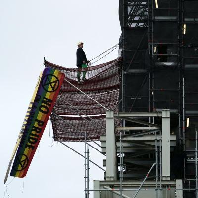 """Mielenosoittaja seisoo Big Ben -kellotornia ympäröivällä rakennustelineellä. Kuvassa myös lippu, jossa teksti """"No Pride""""."""