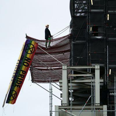 Man i Boris Johnson-peruk uppklättrad i tornet på Big Ben. Regnbågsfärgad flagga hänger i en byggställning.