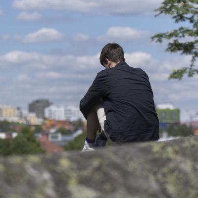 Nuori mies istuu kalliolla. Taustalla siintää taloja ja taivas.
