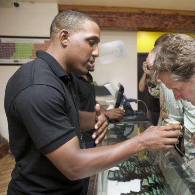 Asiakas haistelee myyjän pitelemää kannabisnäytettä Cannabis City -myymälässä Seattlessa.