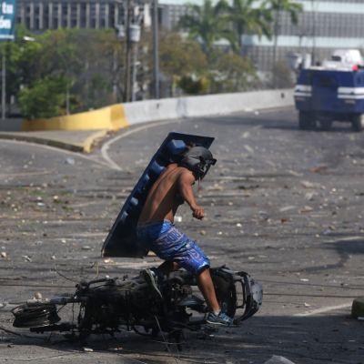 En sköldförsedd demonstrant springer förbi en utbränd motorcykel under kravellerna i Caracas