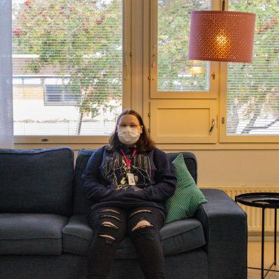 En kvinna med munskydd sitter på en soffa. Hon håller händerna i munktröjans fickor och tittar in i kameran.