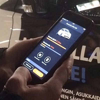 miehen kädessä älypuhelin jossa auki auton vuokraamiseen tarkoitettu sovellu, taustalla sähköauto