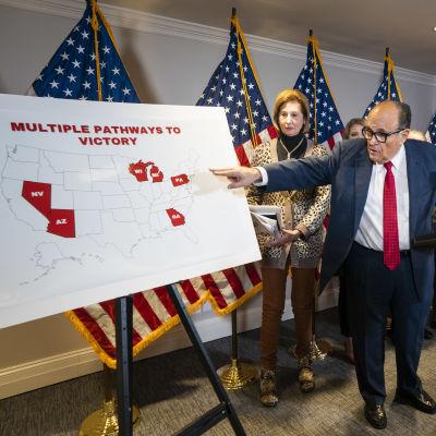 Man i kostym pekar på karta över USA. Mannen är Trumps advokat Rudy Giuliani.