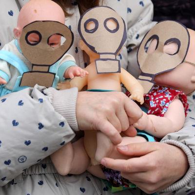 Lapsi pitelee sylissään kolmea vauvanukkea, joiden kasvoilla on paperiset kaasunaamarit.