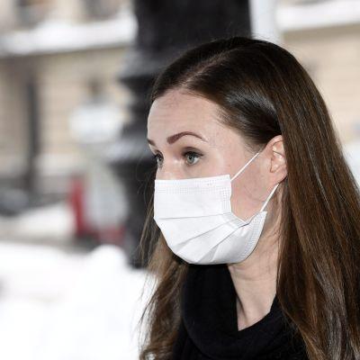 Sanna Marin i munskydd utanför Ständerhuset.