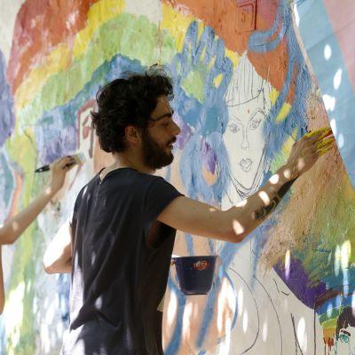 Deltagare i Istanbul Pride målar regnbågsfärger på en vägg i Istanbul den 24 juni 2017. En transflagga i ljusblått, ljusrött och vitt hänger i förgrunden.