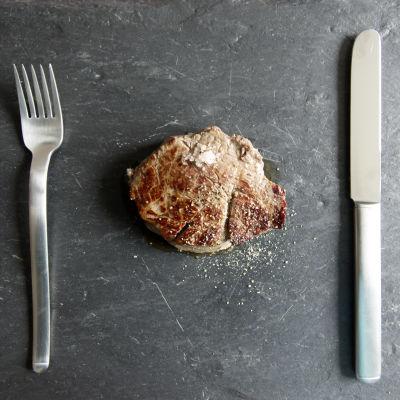 Bild på en biff på ett fat med kniv och gaffel på sidan om.