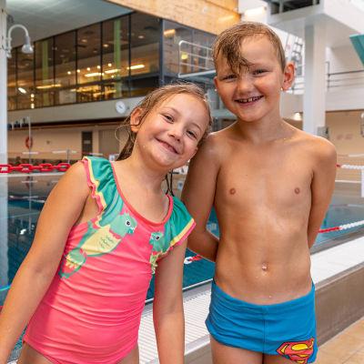 En flicka och en pojke framför en hoppbassäng.