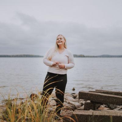 Riikka Grå poseeraa rantamaisemassa