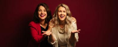Två leende kvinnor framför röd vägg