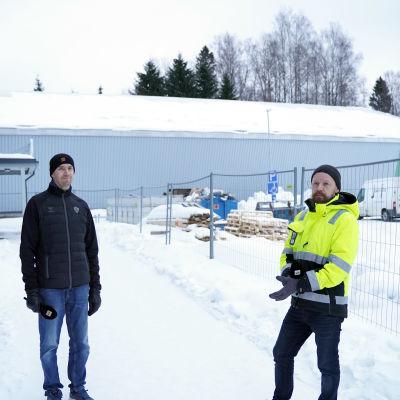 två män i snön framför bollhall